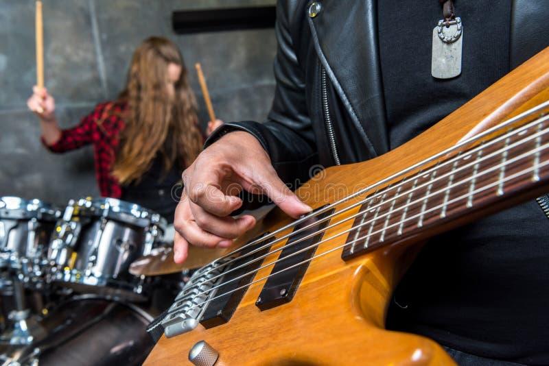 Punto di vista parziale dell'uomo che gioca chitarra con la donna che gioca i tamburi dietro fotografia stock