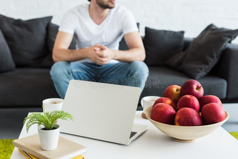 punto di vista parziale dell'uomo che si siede sullo strato vicino alla tavola con le tazze di caffè, il computer portatile, i li fotografie stock libere da diritti