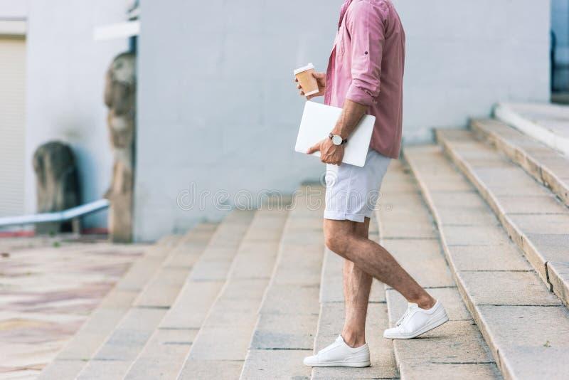 punto di vista parziale dell'uomo con il computer portatile ed il caffè da andare camminare sui punti sulla via fotografia stock