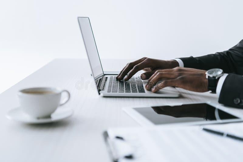 punto di vista parziale dell'uomo d'affari afroamericano che scrive sul computer portatile nel luogo di lavoro fotografia stock libera da diritti