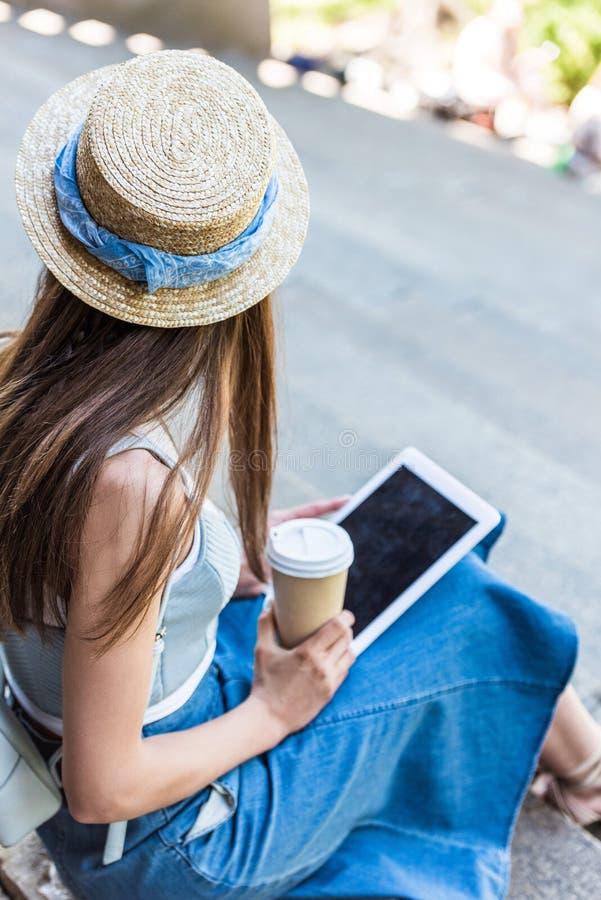 punto di vista parziale della donna con la compressa ed il caffè da andare sedersi sui punti sulla via immagine stock