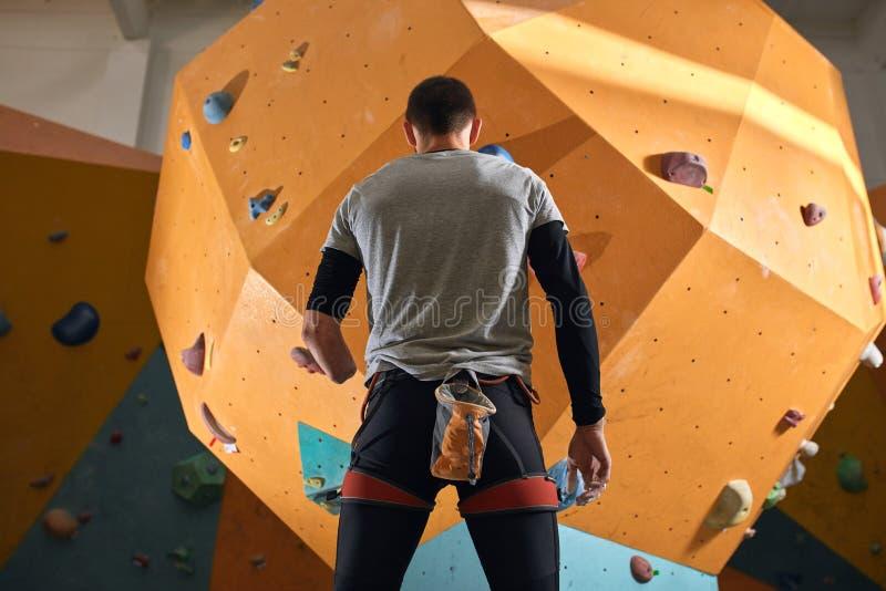 Punto di vista posteriore di angolo basso dello sportivo fisicamente alterato che fissa alla parete rampicante fotografia stock libera da diritti