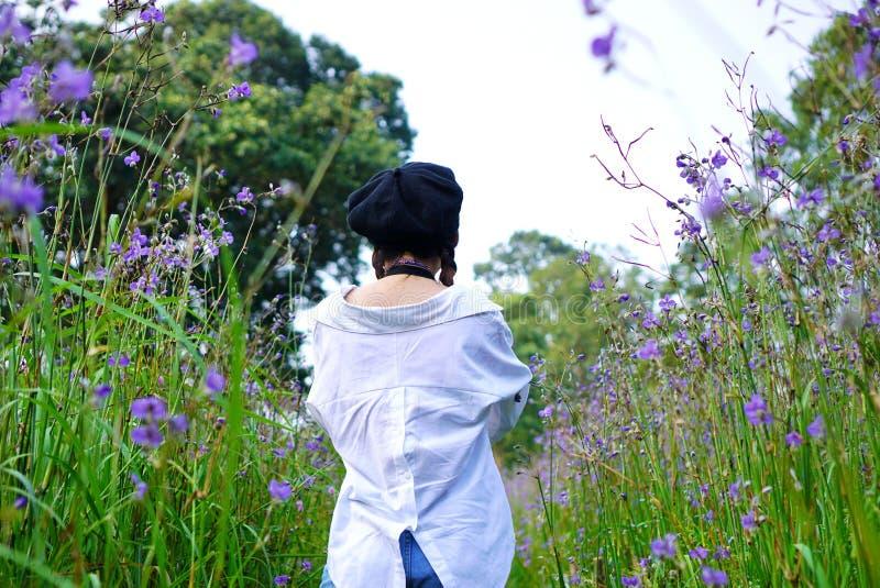 Punto di vista posteriore di bella donna in giardino floreale fotografie stock libere da diritti
