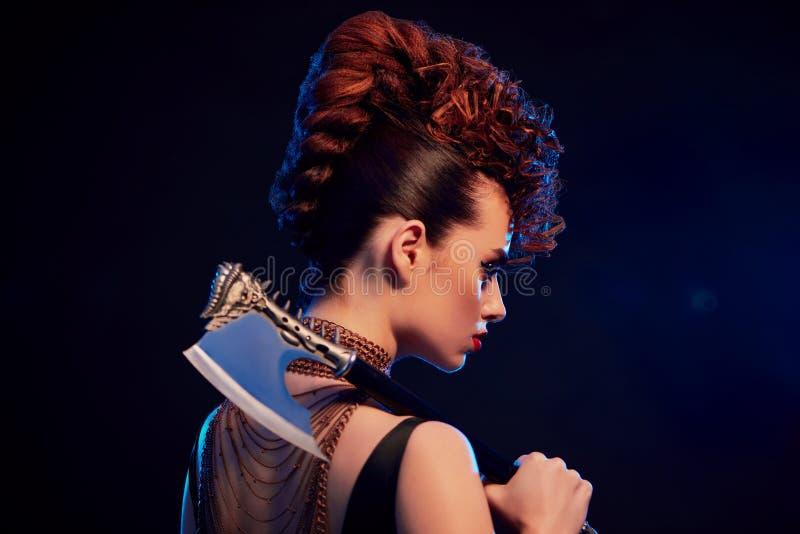 Punto di vista posteriore di bella ragazza del guerriero che tiene ascia tagliente con le spine fotografia stock