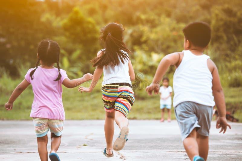 Punto di vista posteriore dei bambini asiatici divertendosi da funzionare insieme e giocare fotografia stock