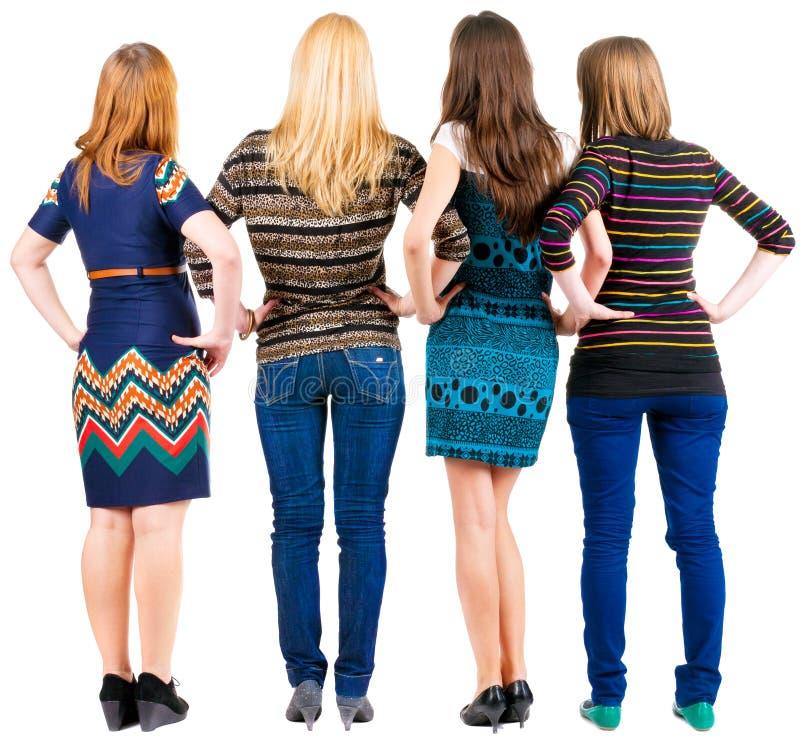 Punto di vista posteriore del gruppo di giovani donne che discutono e che guardano fotografia stock