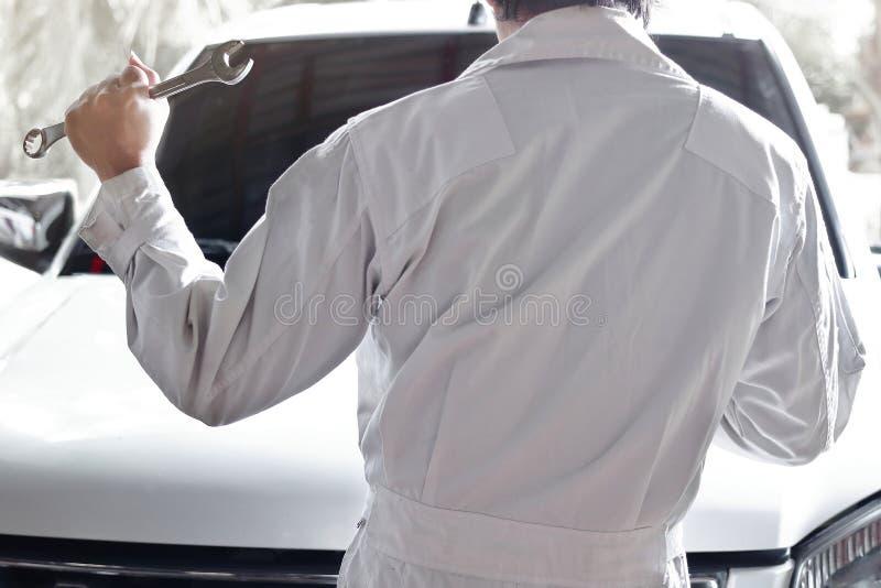 Punto di vista posteriore del meccanico automobilistico in uniforme con la chiave che diagnostica motore al garage di riparazione fotografie stock libere da diritti