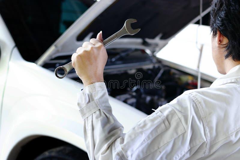 Punto di vista posteriore del meccanico professionista in uniforme con la chiave che ripara motore sotto il cappuccio dell'automo fotografia stock