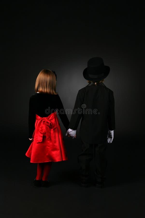 Punto di vista posteriore del ragazzo e della ragazza in vestiti convenzionali immagini stock