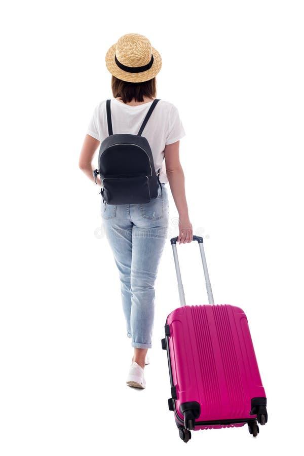Punto di vista posteriore del turista femminile che cammina con la valigia isolata su bianco fotografia stock libera da diritti