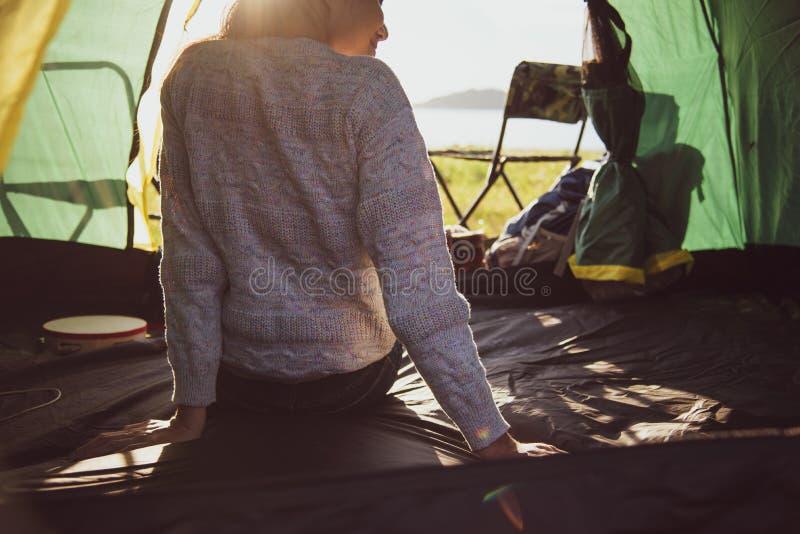 Punto di vista posteriore del turista femminile felice che si rilassa in tenda di campeggio con fotografia stock