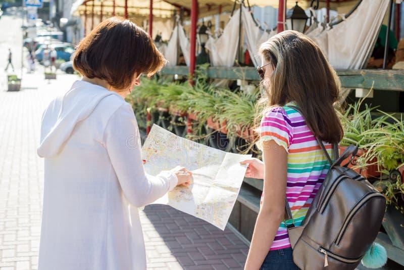 Punto di vista posteriore del turista teenager della figlia e della mamma che esamina la mappa sopra fotografia stock libera da diritti