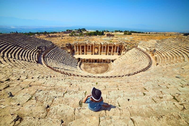 Punto di vista posteriore del viaggiatore della donna in cappello che esamina le rovine di stupore dell'anfiteatro in Hierapolis  immagini stock libere da diritti