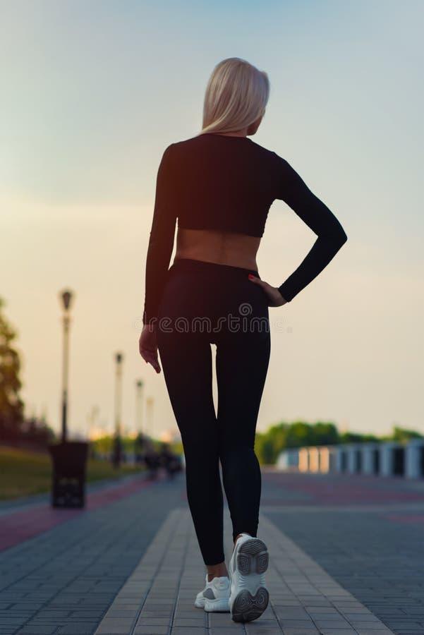 Punto di vista posteriore dell'atleta attraente sexy della giovane donna che corre all'aperto nel tramonto fotografie stock