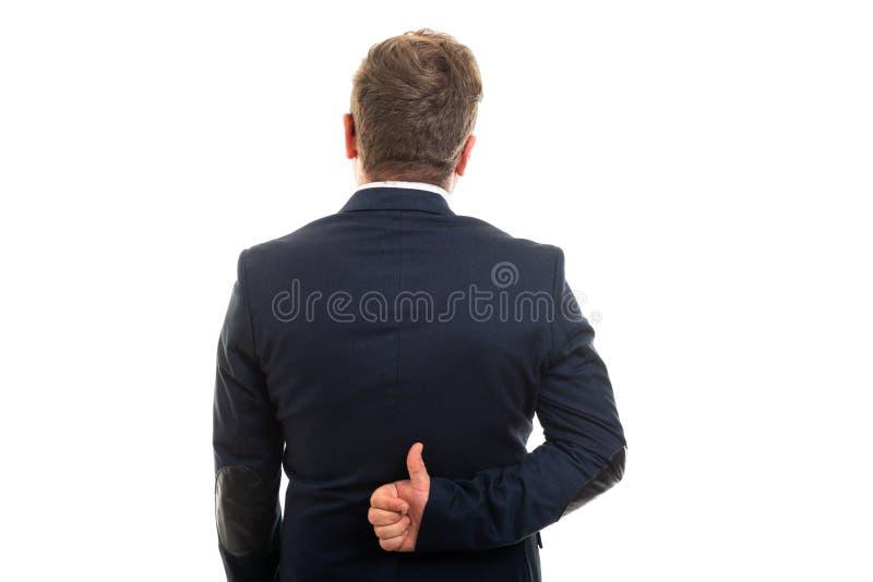 Punto di vista posteriore dell'uomo di affari che mostra pollice sul gesto immagine stock