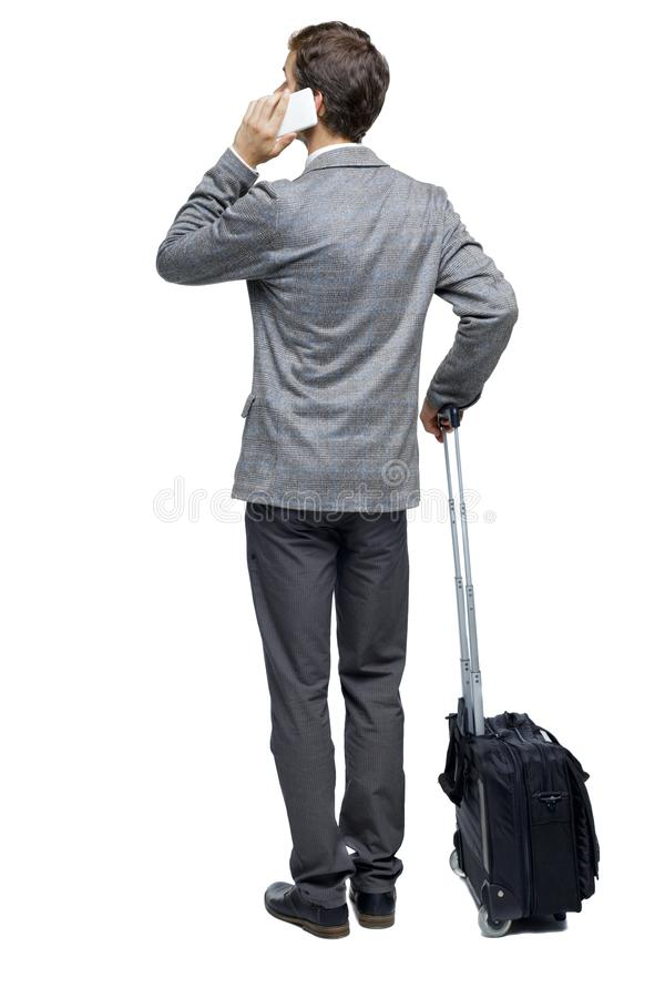 Punto di vista posteriore dell'uomo di affari con la valigia che parla sul telefono immagine stock