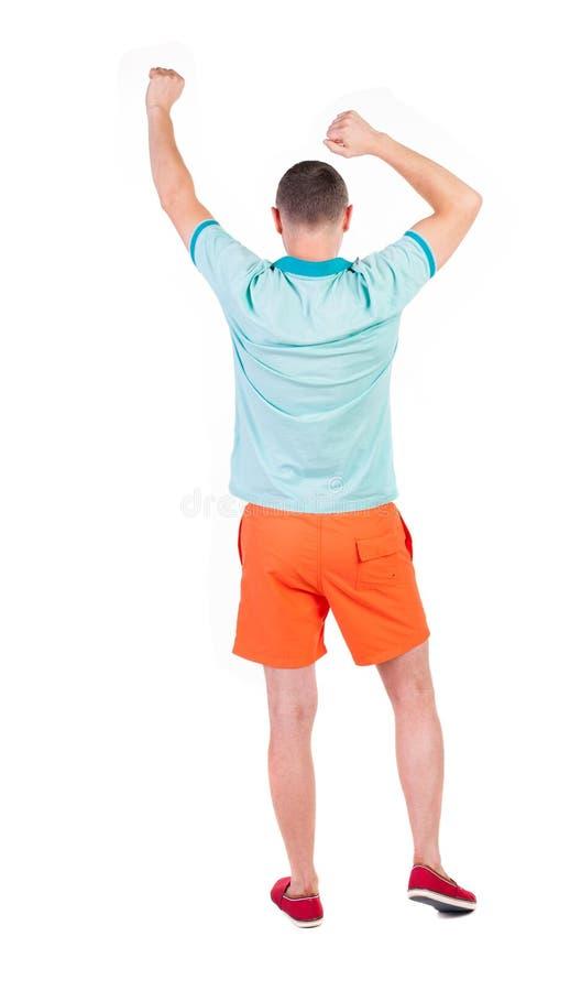 Punto di vista posteriore dell'uomo allegro che celebra le mani di vittoria su fotografia stock
