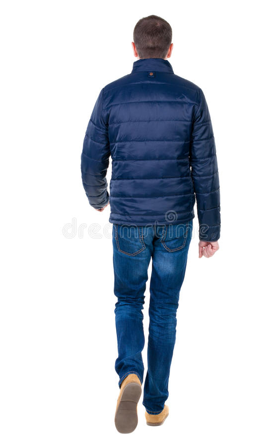 Punto di vista posteriore dell'uomo bello andante in jeans e rivestimento fotografia stock