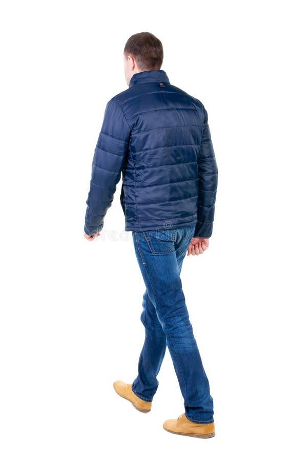 Punto di vista posteriore dell'uomo bello andante in jeans e rivestimento fotografie stock