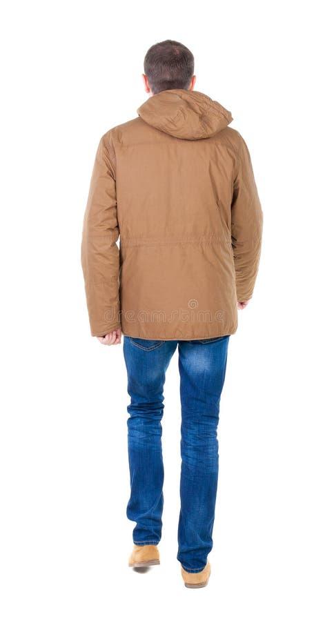 Punto di vista posteriore dell'uomo bello andante in parka marrone fotografia stock libera da diritti