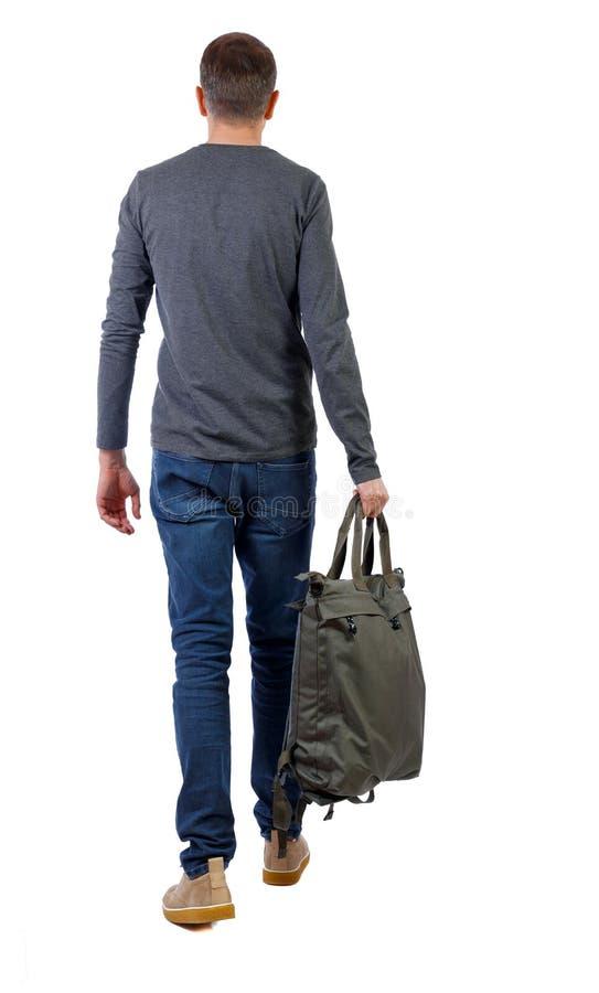 Punto di vista posteriore dell'uomo di camminata con la borsa verde fotografia stock