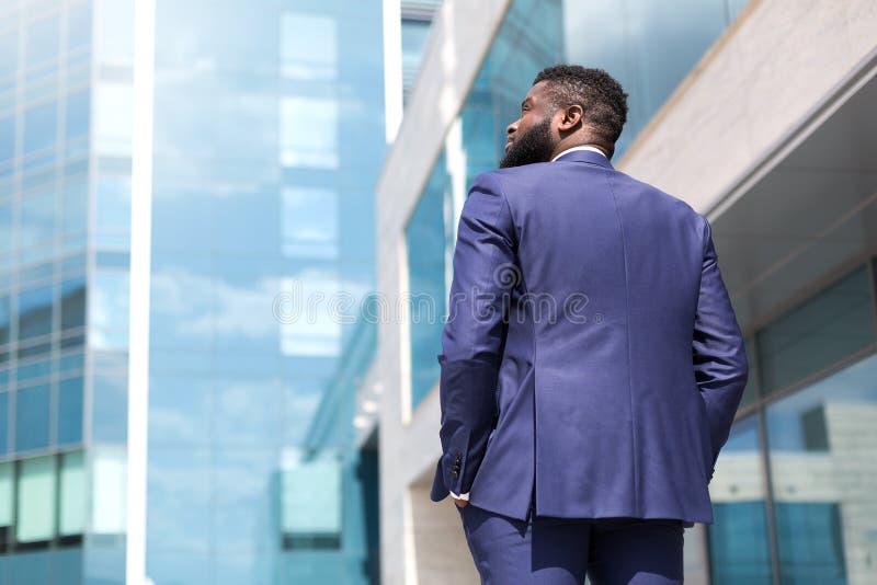 Punto di vista posteriore dell'uomo d'affari afroamericano che cammina lungo le grandi finestre dell'ufficio all'aperto Sparato d immagini stock