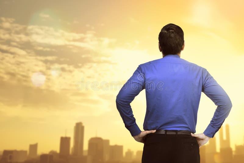 Punto di vista posteriore dell'uomo d'affari che esamina vista di tramonto immagine stock libera da diritti