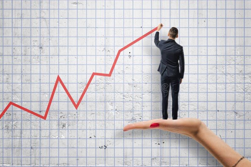 Punto di vista posteriore dell'uomo d'affari che traccia un diagramma rosso che sta sul woman& x27; mano di s immagini stock
