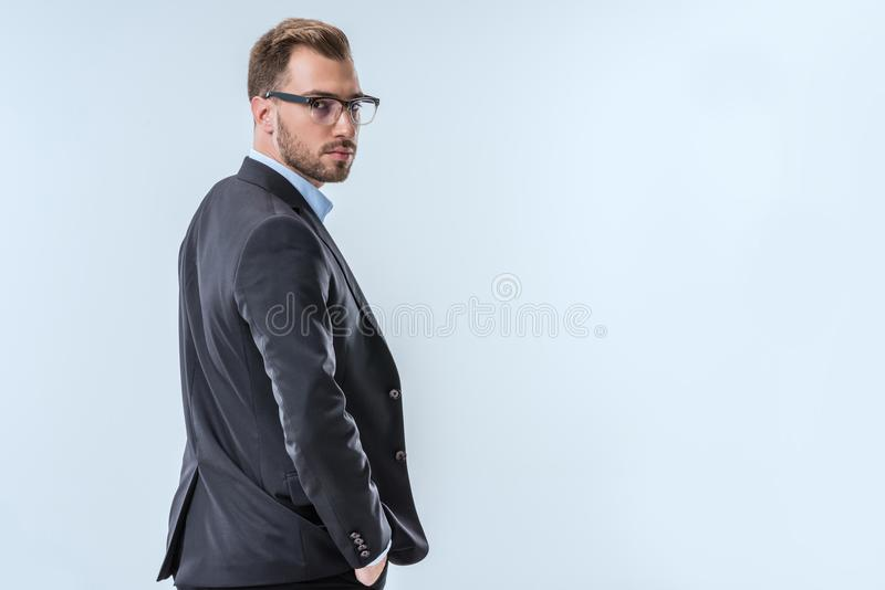 punto di vista posteriore dell'uomo d'affari sicuro in occhiali e nell'usura convenzionale che esaminano macchina fotografica immagini stock libere da diritti