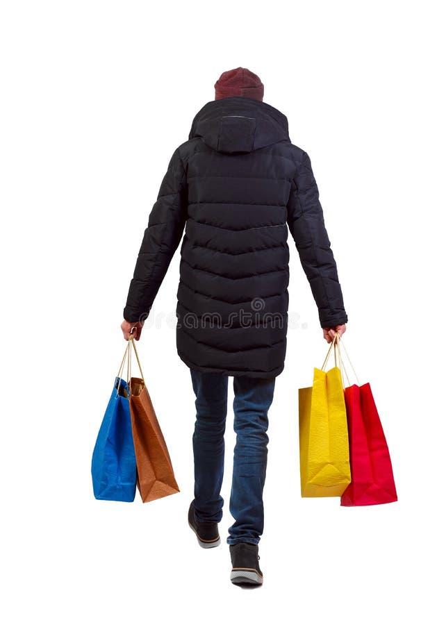 Punto di vista posteriore dell'uomo in rivestimento di inverno con i sacchetti della spesa immagine stock