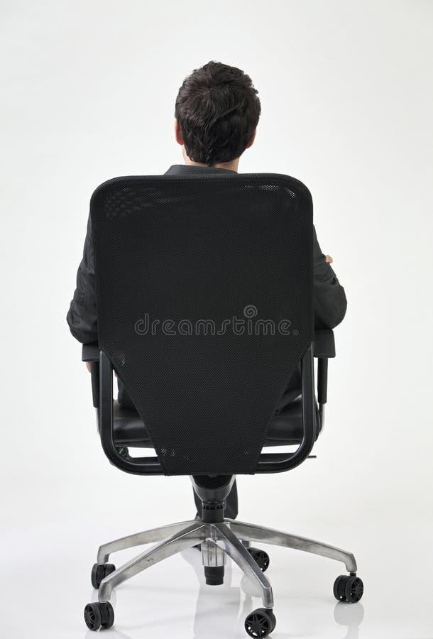 Punto di vista posteriore dell'uomo sulla presidenza fotografia stock libera da diritti