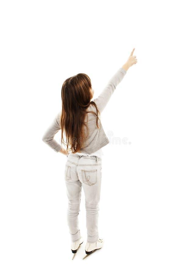 Punto di vista posteriore della bambina con i pattini da ghiaccio, punti alla parete fotografia stock libera da diritti