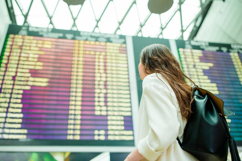 Punto di vista posteriore della donna in aeroporto internazionale che esamina il bordo di informazioni di volo che controlla per  fotografia stock libera da diritti