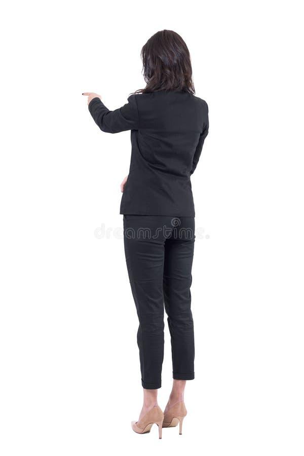 Punto di vista posteriore posteriore della donna di affari in vestito che interagisce con il touch screen o che indica dito alla  fotografia stock