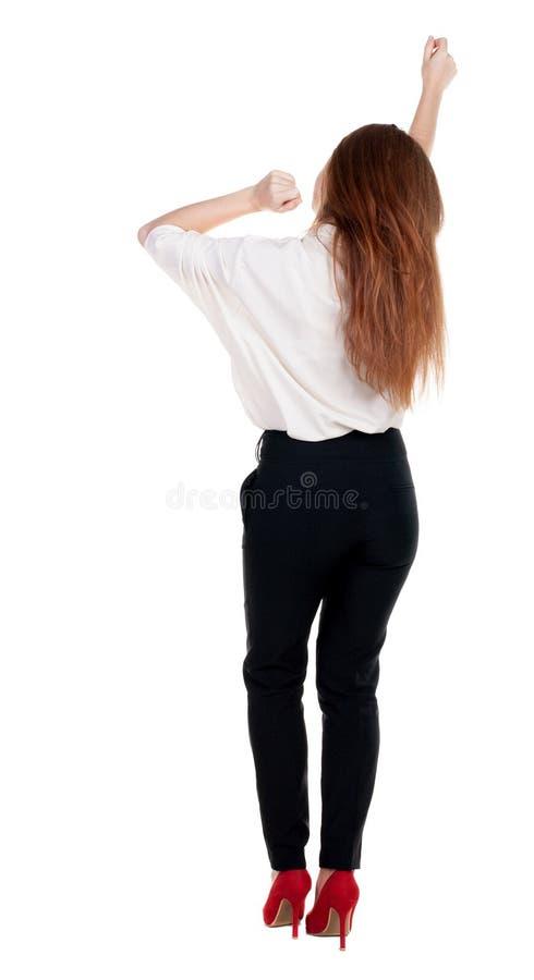 Punto di vista posteriore della donna allegra che celebra le mani di vittoria su immagine stock