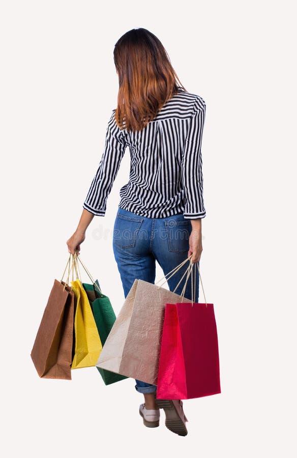 Punto di vista posteriore della donna andante con le borse di acquisto immagini stock libere da diritti
