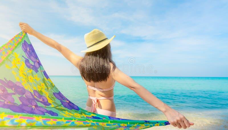 Punto di vista posteriore della donna asiatica adulta portare il cappello rosa di paglia e del bikini che si rilassa e che gode d immagini stock