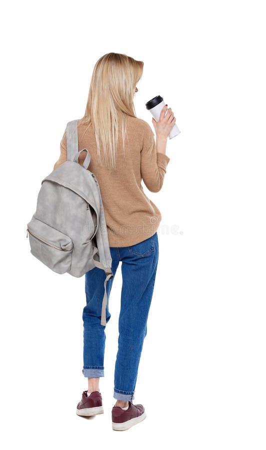 Punto di vista posteriore della donna di camminata con la tazza di caffè e lo zaino fotografie stock