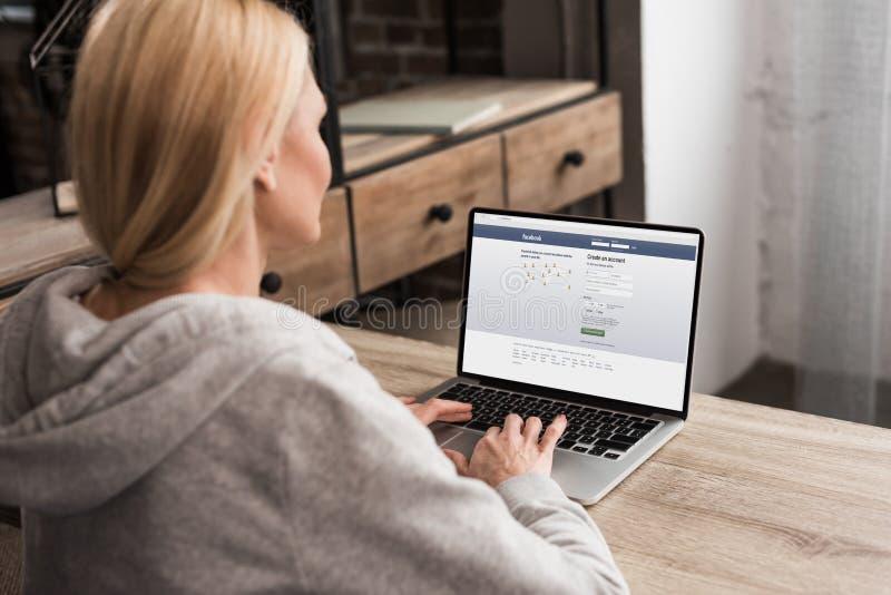 punto di vista posteriore della donna che per mezzo del computer portatile con il sito Web della rete sociale del facebook fotografia stock