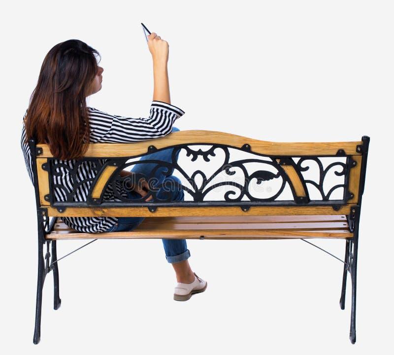 Punto di vista posteriore della donna che si siede sul banco e sugli sguardi allo schermo la compressa fotografie stock