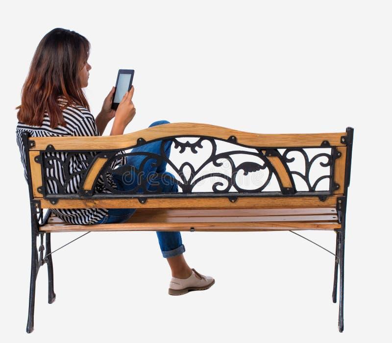 Punto di vista posteriore della donna che si siede sul banco e sugli sguardi allo schermo la compressa immagini stock libere da diritti