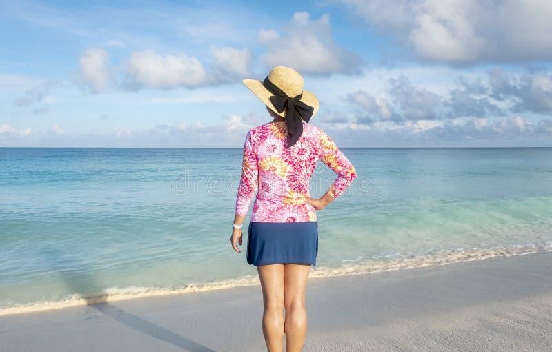 Punto di vista posteriore della donna che sta su una spiaggia caraibica 1 fotografia stock