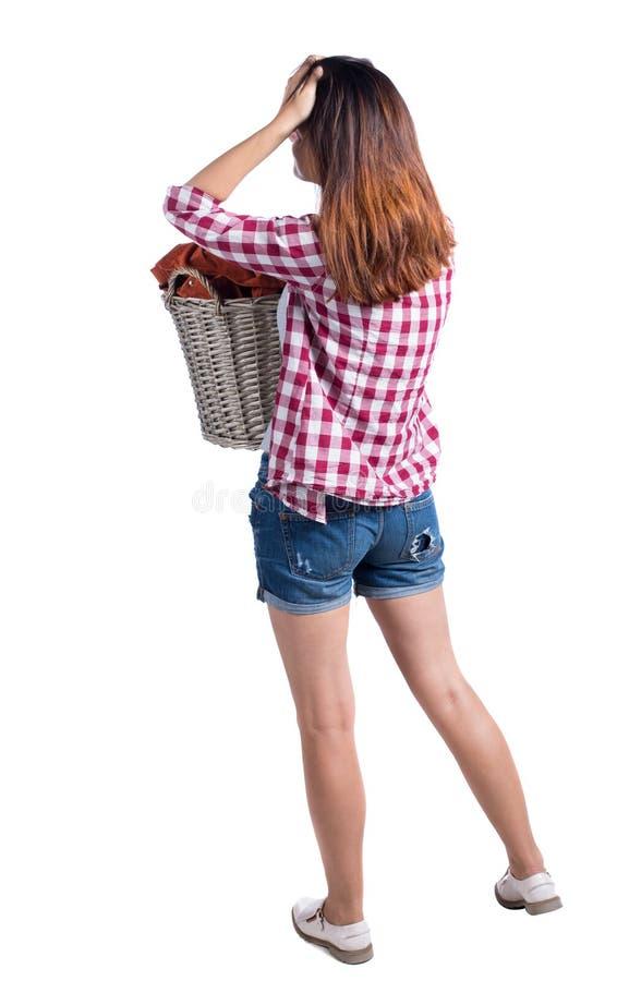 Punto di vista posteriore della donna con il canestro della lavanderia sporca la ragazza è impegnata nel lavaggio fotografia stock libera da diritti