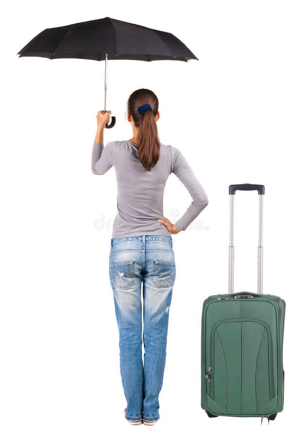 Punto di vista posteriore della donna con l'ombrello che viaggia con i suitcas immagini stock