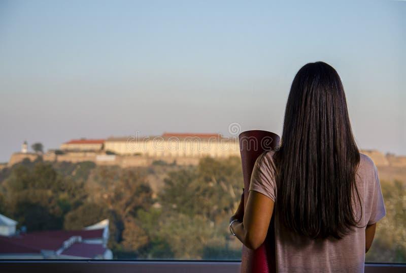 Punto di vista posteriore della donna con la città di sorveglianza della stuoia di yoga attraverso la finestra fotografie stock