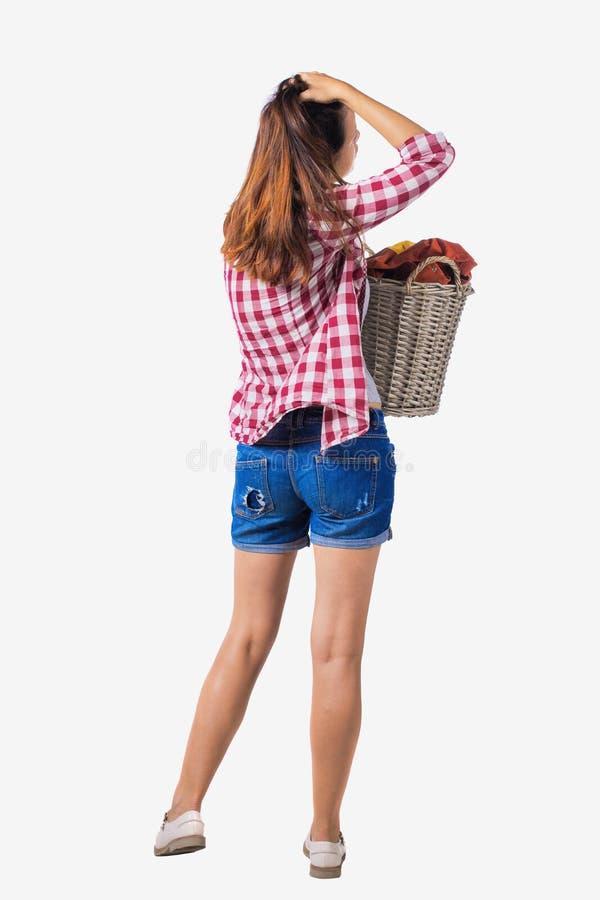 Punto di vista posteriore della donna con la lavanderia sporca del canestro la ragazza è impegnata nel lavaggio immagini stock libere da diritti