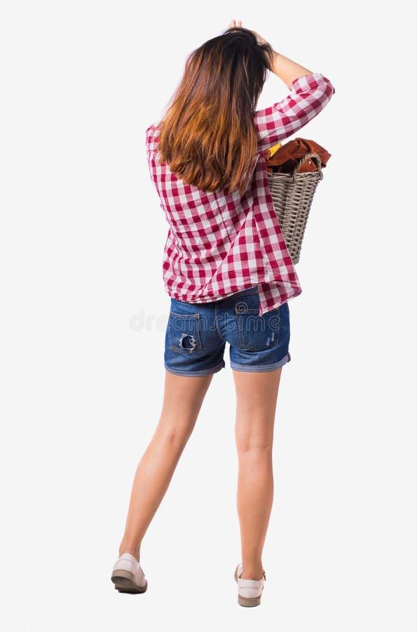 Punto di vista posteriore della donna con la lavanderia sporca del canestro la ragazza è impegnata nel lavaggio fotografia stock libera da diritti