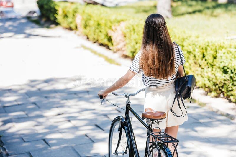punto di vista posteriore della donna con la retro bicicletta che cammina sulla via immagine stock