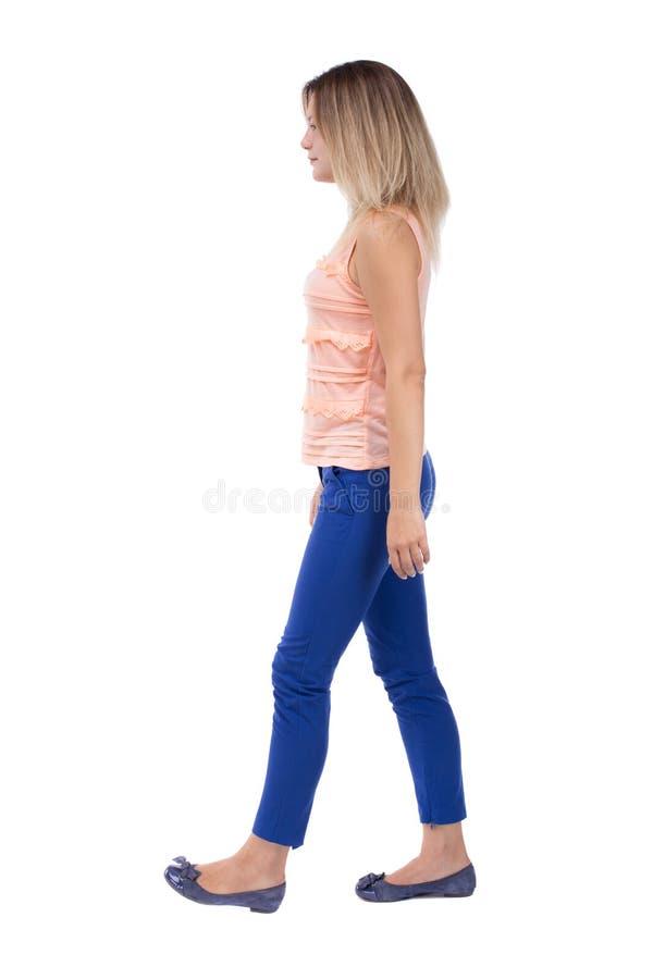 Punto di vista posteriore della donna di camminata bella ragazza bionda nel moto B immagine stock