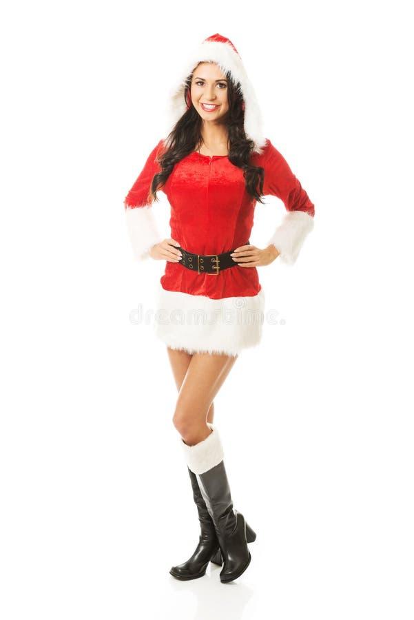 Punto di vista posteriore della donna di Santa che sta con le mani sulle anche, esaminante la macchina fotografica immagine stock